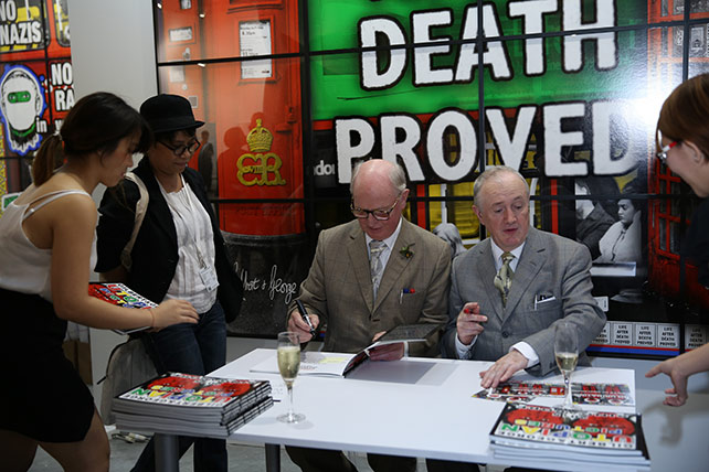 Gilbert & George, signing their catalogues at Art Stage Singapore