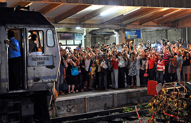 The crowd cheering and clicking their cameras as the engine for the 2nd last arriving Malayan Railway (KTM) train pulled into the Tanjong Pagar Railway station on 30 June 2011, which is the last day of operation for the station. From 1 July 2011, the trains will start and end their journeys at Woodlands Train Checkpoint in the north. ST Photo: Raj Nadarajan