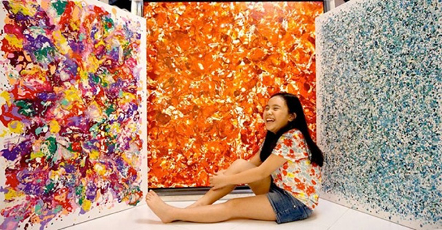 Ashley Ann in front of her artworks